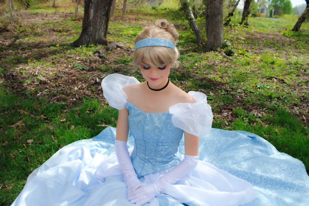 Cinderella in her ball gown sitting in a forest